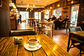 テーブルと blured カフェでコーヒー
