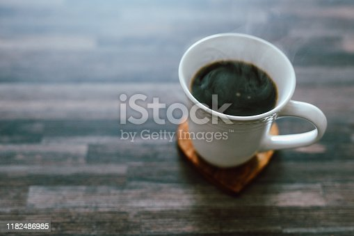 Shot of a cup of freshly made coffee on a table at home
