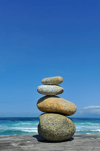 Cairn of Zen stones stacked at beach sea blue sky stock photo