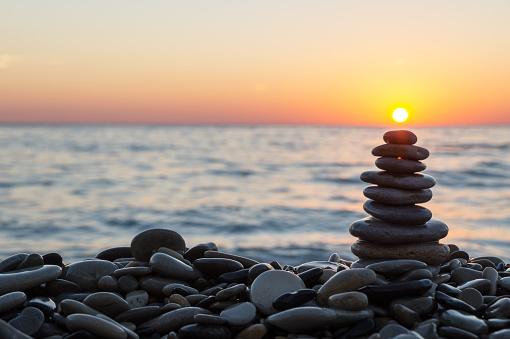 Cairn stones with sun on the beach on sundown