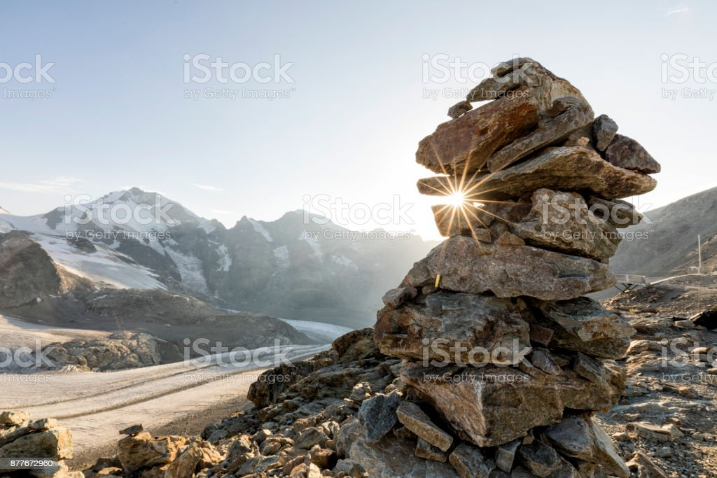 Cairn with sunray in the alps with glacier in the background, Diavolezza, Engandin, Switzerland stock photo
