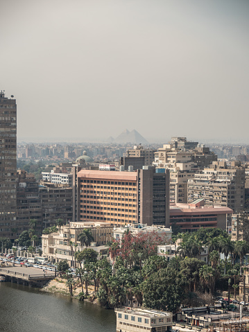 High angle view of Cairo city with a dramatic sunset on the background. Pyramids in distance