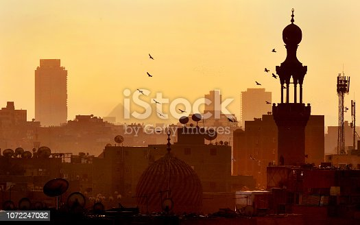 The skyline of Cairo at sunset with birds over domes and satellite dishes with distant pyramids at Giza
