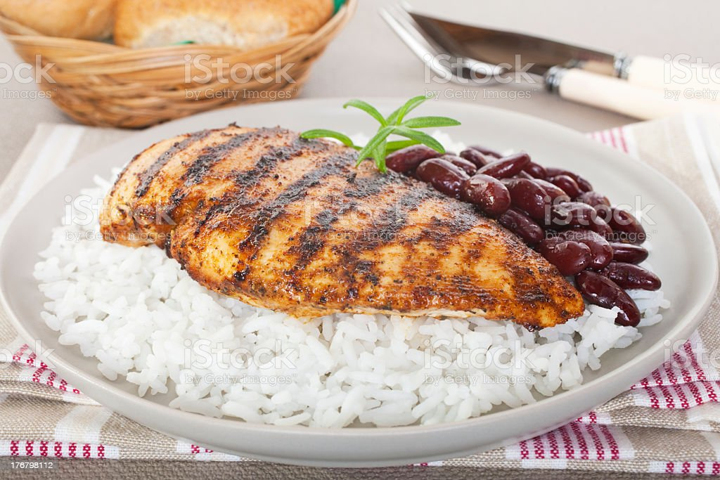 Cajun chicken with rice and beans on a white plate stock photo