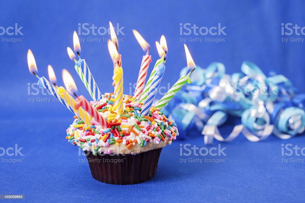 Cake and Candles: Birthday cupcake with many burning candles. Sprinkles. royalty-free stock photo