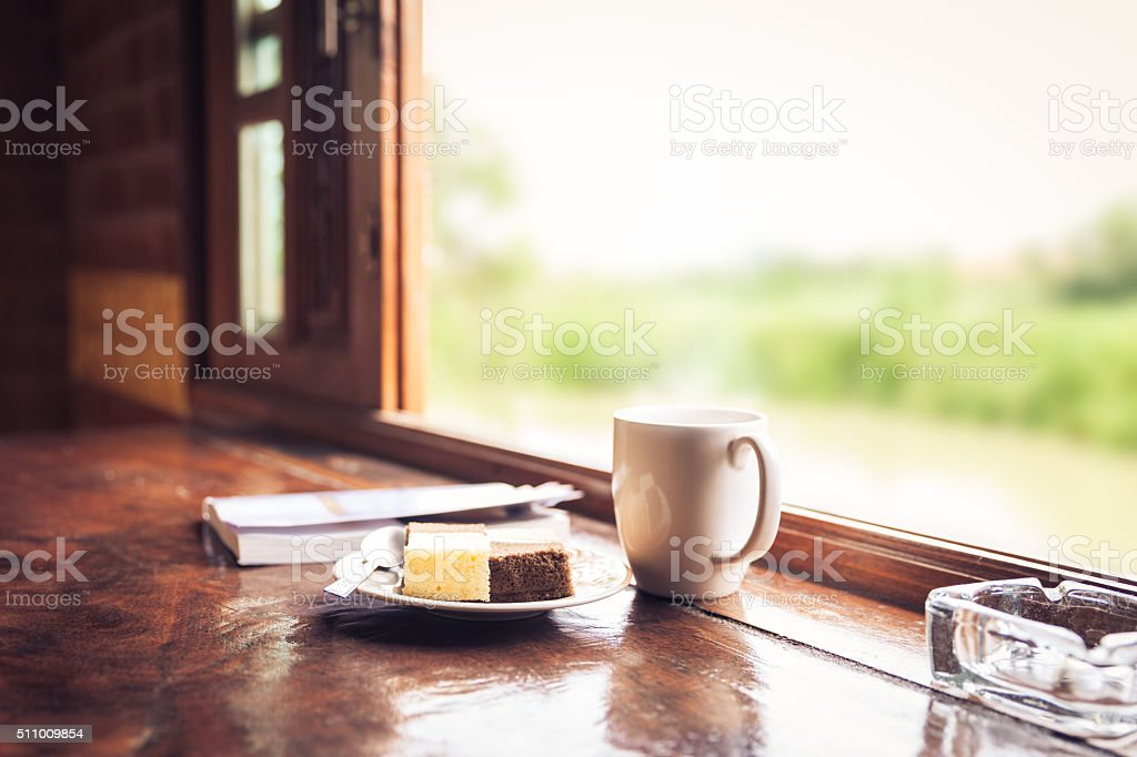 Cake and coffee cup on wooden table near window sill. stock photo