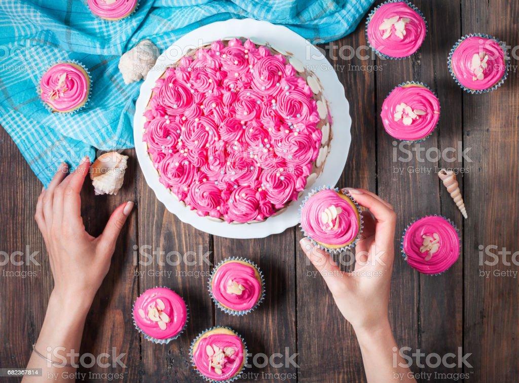 Tårta och cupcakes med rosa grädde på rustika trä bakgrund. royaltyfri bildbanksbilder