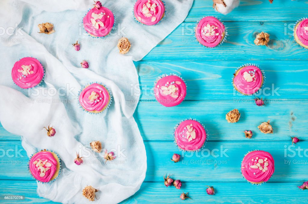 Cake and cupcakes with pink cream on rustic wood background. royalty-free stock photo