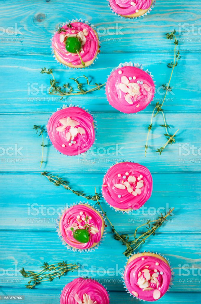 Cake and cupcakes with pink cream on rustic wood background. zbiór zdjęć royalty-free