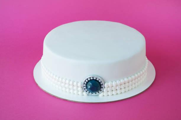 kuchen backen mit weißen mastix verziert mit perlen aus perlen, schmuck aus stein auf rosa hintergrund. - prinzessinnen torte stock-fotos und bilder