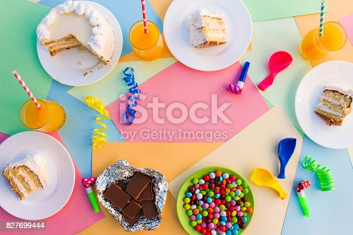 istock Cake, candy, chocolate, whistles, streamers, balloons, juice on holiday table. Concept of children's birthday party. View top. 827699444