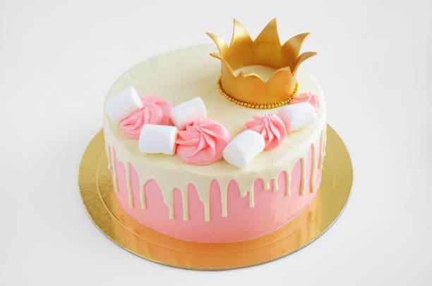 kuchen für kleine mädchen mit rosa sahne, weiße schokolade, mit marshmallow und gold krone geschmückt. - prinzessinnen torte stock-fotos und bilder
