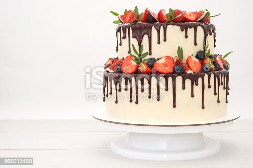 istock Cake in chocolate, decorated with berries. 866213450