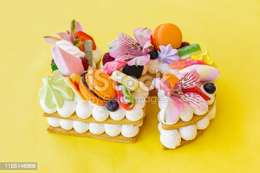 Close-up of a cake in shape of number five abundantly decorated with candies