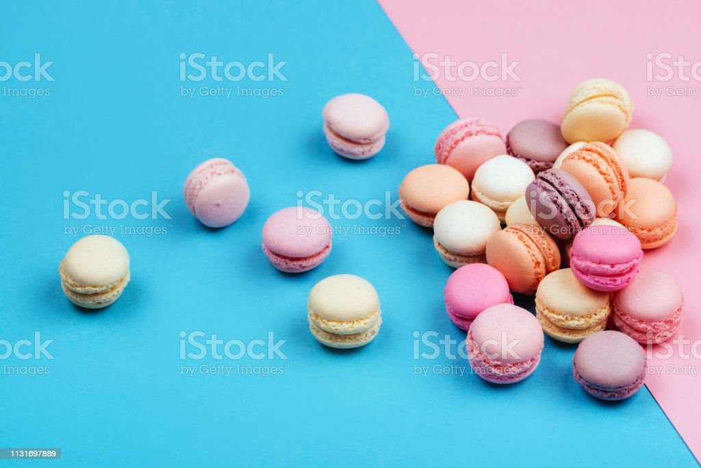 Cake macaron or macaroon on pink and blue background. stock photo