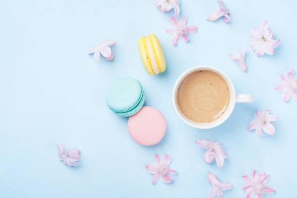 kuchen-macaron oder makronen, rosa blüten und kaffee auf blau pastell hintergrund ansicht von oben. kreative und mode zusammensetzung. flache laien stil. - modetorten stock-fotos und bilder