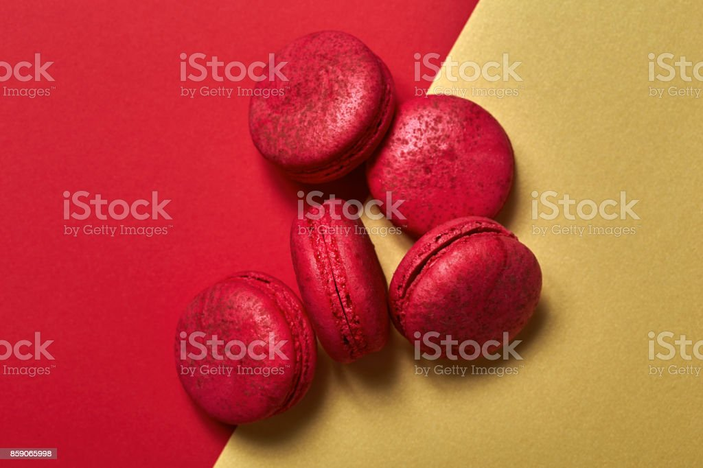 Cake macaroons on red and gold background from above, almond cookies, top view stock photo