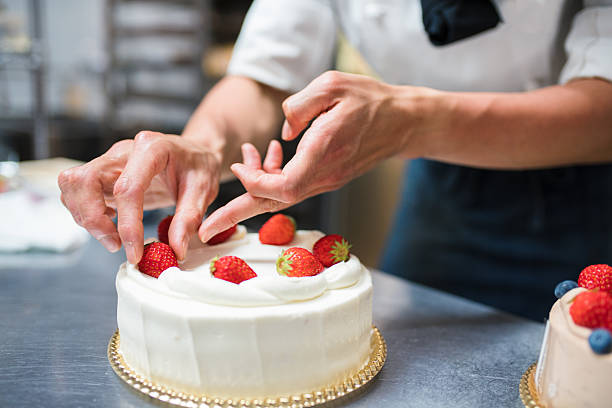 Cake maker placing strawberries on a cake Baker placing strawberries on a freshly finished cake. Kyoto, Japan. May 2016 decorating a cake stock pictures, royalty-free photos & images