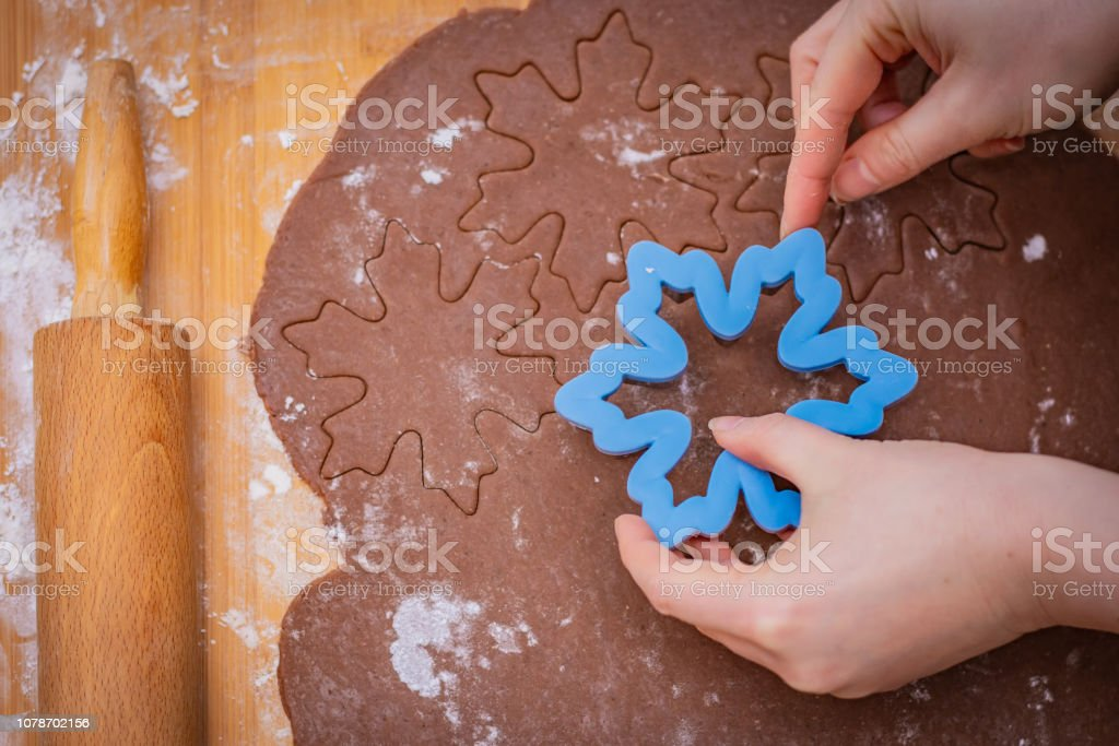 Cake spread on a countertop with starred hands, hands hold the form, the rolling pin lies on the edge – zdjęcie