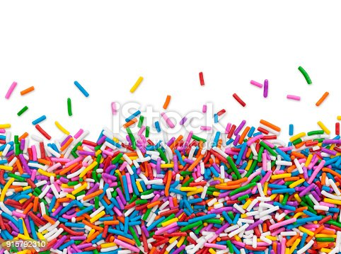 Multi colored cake sprinkles bottom border isolated on white (excluding the shadow) for the top white part