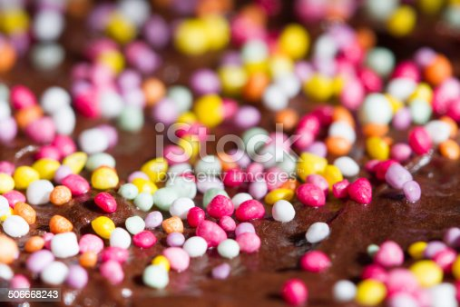 Closeup macro shot of bright pink, yellow and pastel green nonpareils (tiny round sweets or sprinkles) on shiny dark chocolate icing. Bottom third of photograph in focus, the rest blurred.