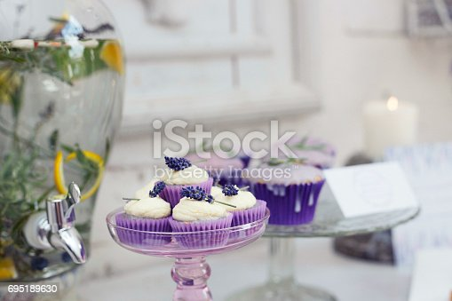 istock Cake stand with mini cupcakes with mascarpone frosting and fresh lavender flowers. 695189630