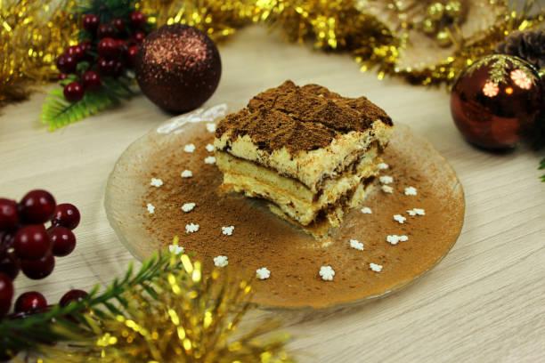 kuchen tiramisu auf eine platte nahaufnahme im schnitt auf einem hölzernen hintergrund mit weihnachtsschmuck - weihnachtlich tiramisu stock-fotos und bilder