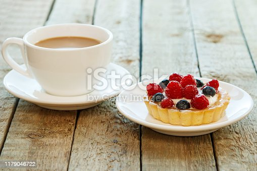 Delicious cake with berries and cup of coffee