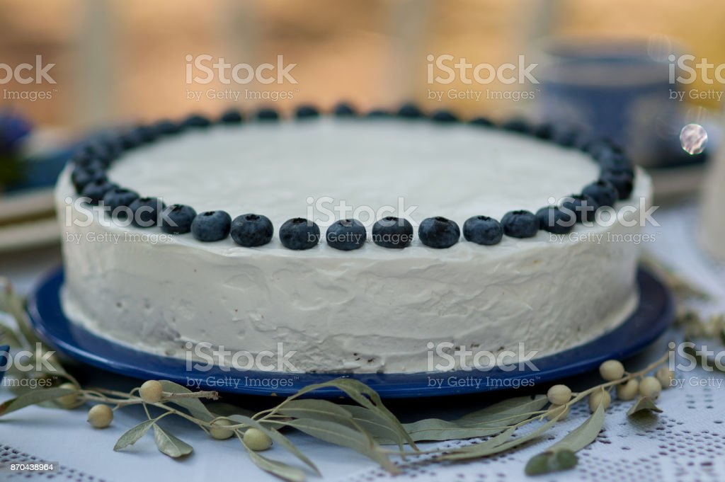 Cake with blue cream for men, decorated with blackberry and blueberry. stock photo
