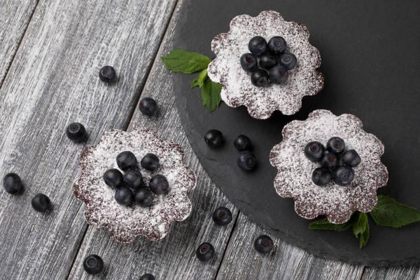 kuchen mit heidelbeeren und zucker puder auf dem tisch. - heiße schokoladen cupcakes stock-fotos und bilder