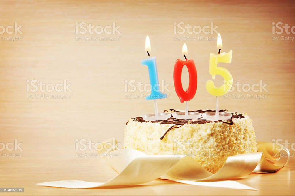 Cake with burning candle as number one hundred and five stock photo