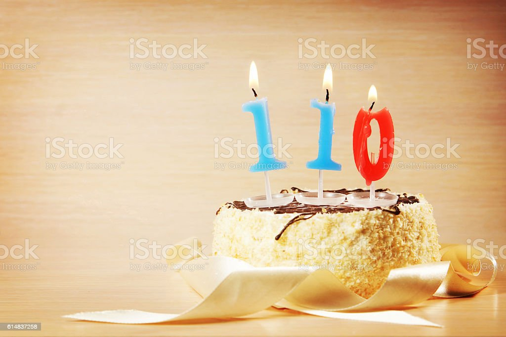 Cake with burning candle as number one hundred and ten stock photo