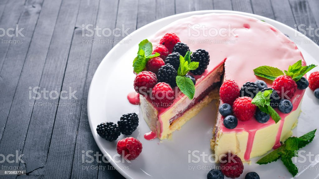 Cake with butter and fresh berries and fruits. Dessert. On a wooden background. Top view. Free space for your text. stock photo