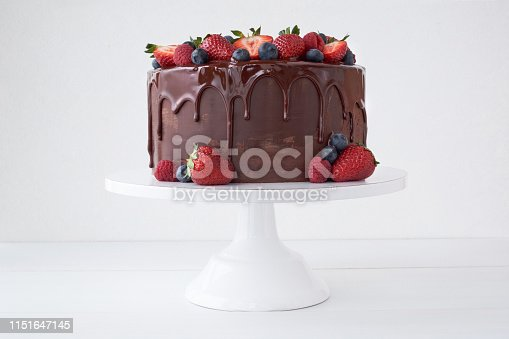 Cake with chocolate, decorated with various berries on a white table. Strawberries, blueberries, raspberries.