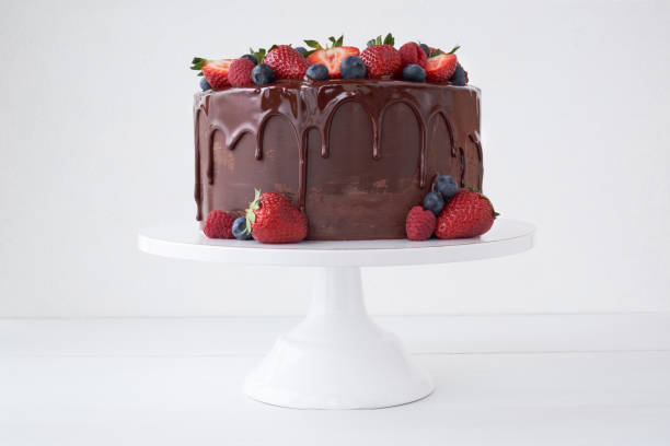 Cake with chocolate, decorated with various berries on a white table. Cake with chocolate, decorated with various berries on a white table. Strawberries, blueberries, raspberries. cake stock pictures, royalty-free photos & images