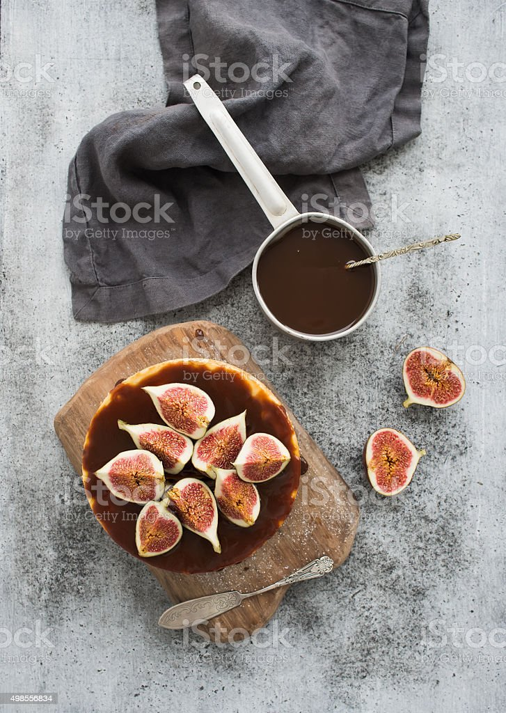 Cake with fresh figs and salted caramel on wooden serving stock photo