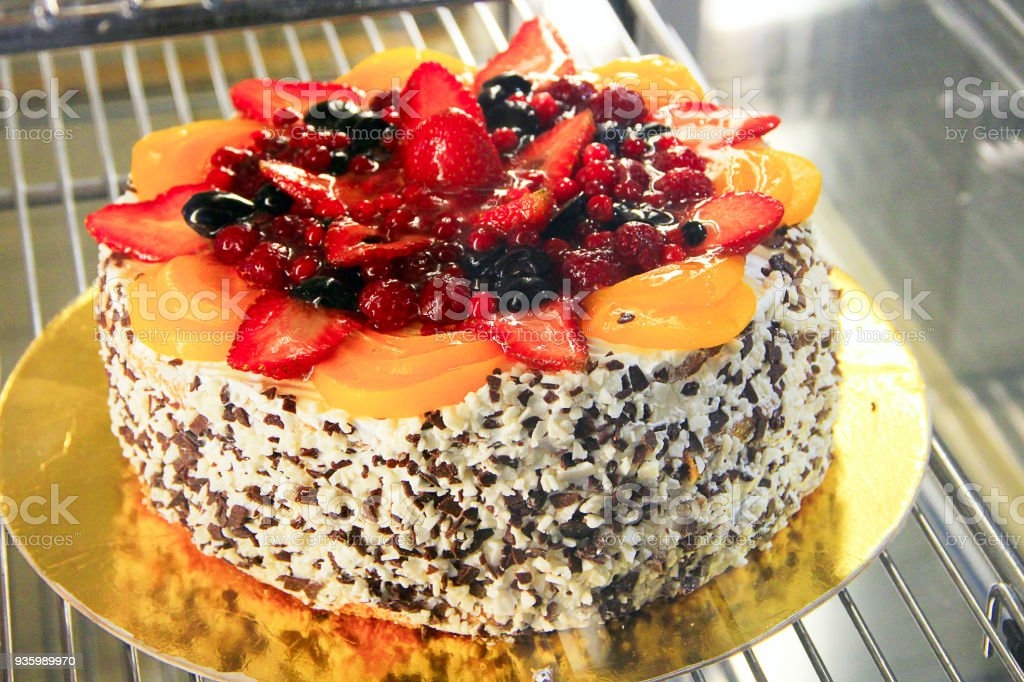 Cake with many berries raspberry apricot currants strawberry on shopwindow stock photo