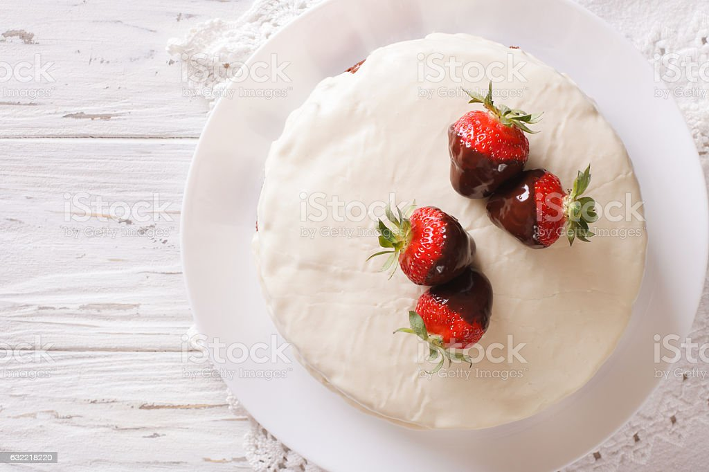 cake with white icing and strawberries in chocolate closeup stock photo