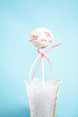 A single cakepop over blue background. The cake is brownie, it has a white cover with small sweets in two colors, pink and white. There is a pink bow in the stick.