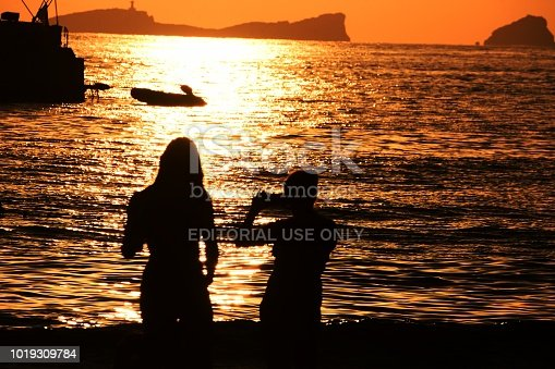 Ibiza ,Spain: July 31 2018, People Silhouette watching a magnificent sunset at  Cala Conta Beach  Ibiza Spain. Location : 07830 Sant Josep de sa Talaia, Balearic Islands, Spain. Ibiza is a small island in the archipelago of the Balearic Islands, Ibiza is known for its nightlife and its desolate beaches