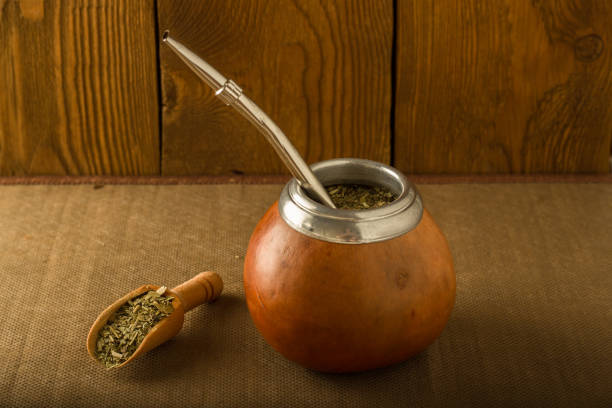 calabash with yerba mate and a wooden spoon against the background of a tree - mate argentino fotografías e imágenes de stock