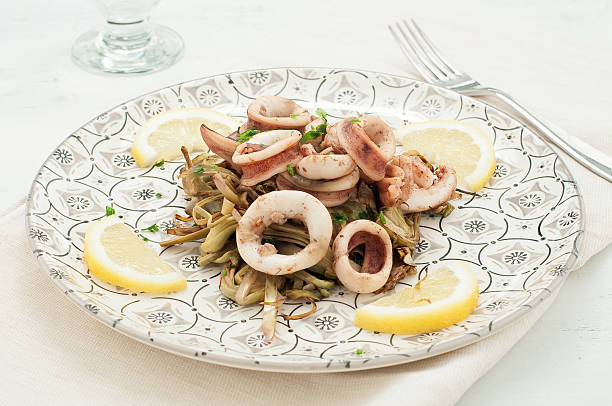 calamari cooked in a pan with the artichokes,italy calamari cooked in a pan with the artichokes,italy cuttlefish stock pictures, royalty-free photos & images