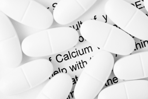 Calcium pills on a letter of DEXA scan results with the word