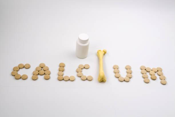 calcium tabletten en fles op witte achtergrond. - calcium stockfoto's en -beelden