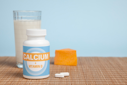 Calcium and vitamin D are important for maintaining bone strength. The focus here is on the calcium bottle and generic label. Other sources of calcium, milk and cheese, are in the background along with copy space.