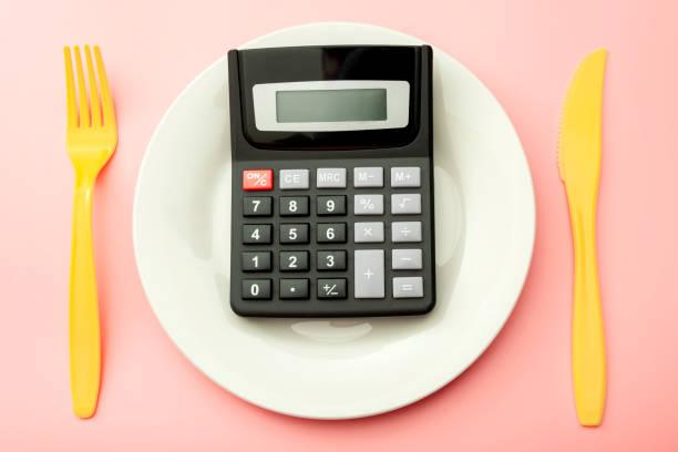 Calcular los costos de gasto de alimentos caros, contar calorías y concepto de programa de pérdida de peso con calculadora en placa vacía, tenedor amarillo y cuchillo aislado en fondo rosa - foto de stock