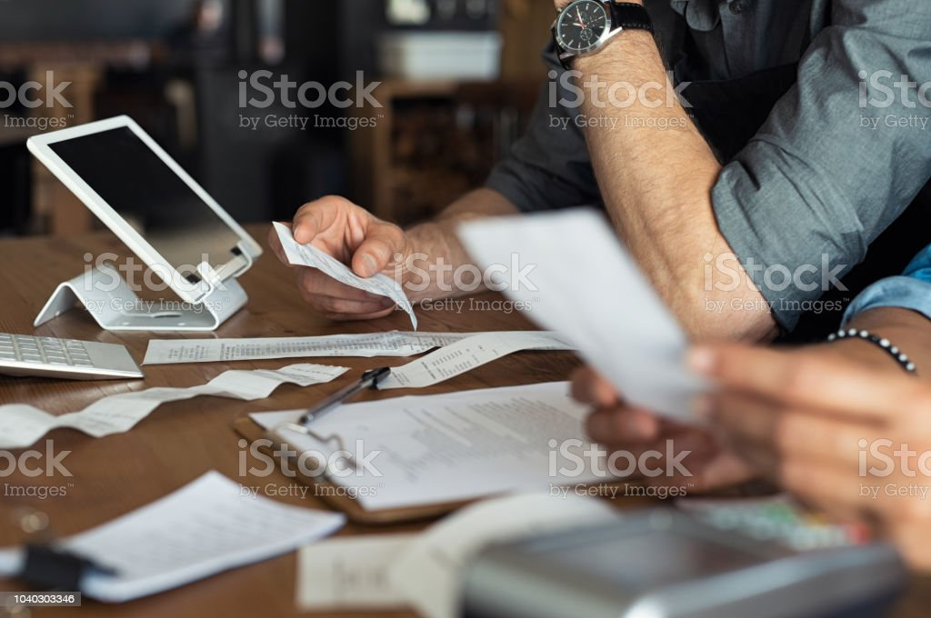 Calculating business expenses Mature smalll business owners calculating finance bills of their activity. Business people using calculator to work. Closeup hands of man and woman calculating bills and expenses. Accountancy Stock Photo