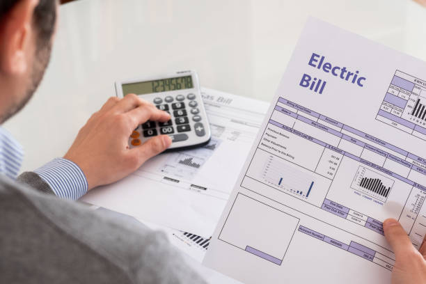 Calculating energy efficiency and energy bill papers stock photo
