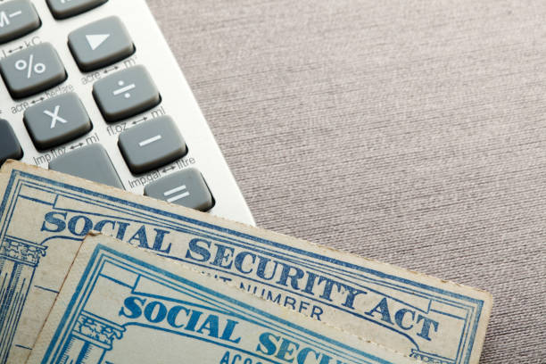 Calculating Your Social Security Benefit Two social security cards rest on top of a calculator which sis on a table top that provides ample room for copy and text. social security stock pictures, royalty-free photos & images