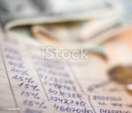 Hand-written calculations, banknotes and coins. Bookkeeping (accounting). Economy. Money savings and budget. Bank deposits.